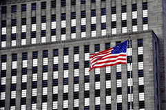 The American Flag. The wind is blowing the American flag which is in front a building Royalty Free Stock Images