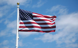 American Flag. A waving American flag flies proudly against the blue summer sky stock image