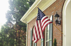 American flag. An American flag hangs from the porch of a brick house Stock Photo
