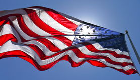 American flag. Sun shining through American flag flying in blue sky Stock Image