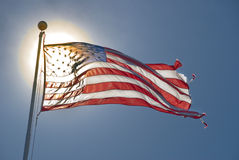 American flag. Back lit by sun against a blue sky Stock Image