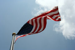 American Flag. Blowing in the wind with clouds behind it Stock Image