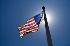 American flag. A flag of the United States hoisted up on a flag pole with the sun directly above it Royalty Free Stock Images