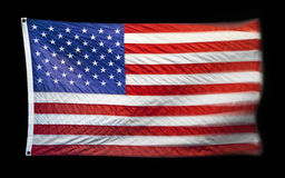 American Flag. An American flag flying with movement and blur isolated on a black background Stock Image