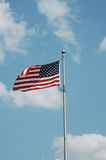 American Flag. Against bright blue sky with coulds stock image