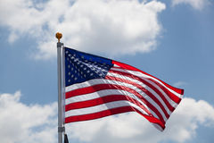 American flag against blue cloudy sky. American flag against blue sky with clouds Royalty Free Stock Images