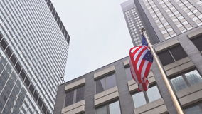 American flag against bright blue sky. American flag against the sky and skyscrapers stock footage