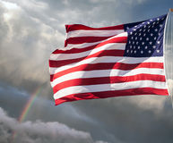 American flag against a cloudy sky with a rainbow Stock Images