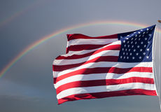 American flag against a cloudy sky with a rainbow Royalty Free Stock Images