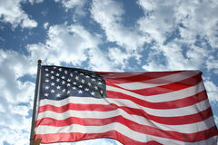 American Flag Against the Sky. Sun-lit American flag blowing in the wind against the clouds Royalty Free Stock Images