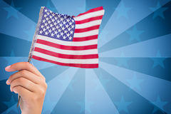 American flag against sunburst. Digitally generated image of human hand holding American flag against sunbrust Royalty Free Stock Photo
