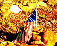 American Flag along a creekside. Small American Flag among rocks stock photo