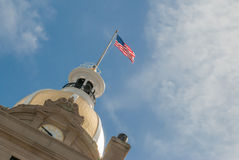 American Flag Atop a Civic Building. The American flag waves atop an urban civic building with a sky background royalty free stock image