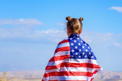 Patriotic holiday. Happy kid, cute little child girl with American flag. USA celebrate 4th of July. stock photography