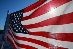 American Flag Backlit on Lake. The stars and stripes of the American flag wave and flutter patriotically backlit by the evening sun next to a lake Royalty Free Stock Photography