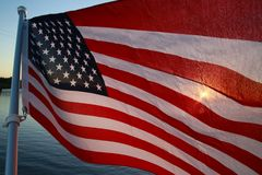 American Flag Backlit Sunset. The stars and stripes of the American flag wave and flutter patriotically backlit by the setting sun next to a lake Stock Images