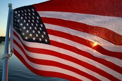 American Flag Backlit Sunset. The stars and stripes of the American flag wave and flutter patriotically backlit by the setting sun next to a lake Royalty Free Stock Photos