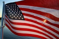 American Flag Backlit Sunset. The stars and stripes of the American flag wave and flutter patriotically backlit by the setting sun next to a lake Royalty Free Stock Photo