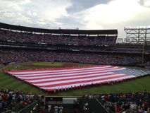 American Flag at the Ballgame. Large American flag stretched across the field at a baseball game Royalty Free Stock Photography