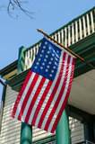 American Flag. An American flag being flown from a traditional porch Stock Images
