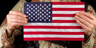 American flag being held by male soldier. Close up horizontal image of United States of America flag with armed male soldier holding it while on black background Royalty Free Stock Images