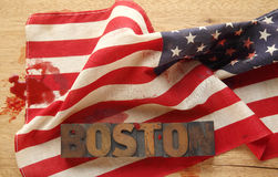 American flag, bloodstains and Boston word in old wood type. The word Boston on a bloodied American flag Stock Images