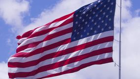 American flag blowing in stiff wind under blue skies. In a stiff wind, the oversized American flag flies in the Macey`s supermarket parking lot in Pleasant Grove stock video footage