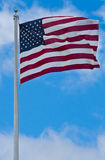 American flag blowing in the wind. With a blue sky background Stock Photo