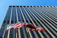 American flag blowing in the wind against commercial building with windows and blue sky Royalty Free Stock Images