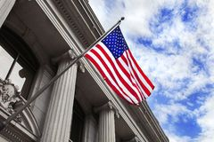 American Flag Blowing in the Wind attached to front of Stone Column Build Royalty Free Stock Image