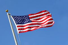 American Flag Blowing in the Wind with Blue Sky Royalty Free Stock Image
