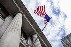 American Flag Blowing in the Wind in Front of Stone Column Build with sky and clouds in background Royalty Free Stock Photo