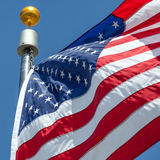 American flag blows in the wind with flag pole. Close-up American flag blows in the wind with flag pole, focus on star of waving flag Stock Photo