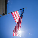 American flag on blue sky with sun Royalty Free Stock Images