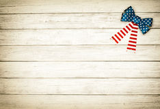 American Flag Bow on White Rustic Board Background with room or space for copy, text.  Horizontal sepia processing. Horizontal of wood slat or planks with one Royalty Free Stock Photo