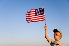 American flag and boy. Young boy holding and looking at American flag with a clear sky background Stock Photos
