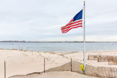 American flag on Breezy Point. American flag on the beach of Breezy Point. Breezy Point is a neighborhood in the New York City borough of Queens, located on the royalty free stock images