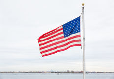 American flag on Breezy Point. American flag on the beach of Breezy Point. Breezy Point is a neighborhood in the New York City borough of Queens, located on the royalty free stock photo