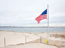 American flag on Breezy Point. American flag on the beach of Breezy Point. Breezy Point is a neighborhood in the New York City borough of Queens, located on the royalty free stock photos