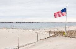 American flag on Breezy Point. American flag on the beach of Breezy Point. Breezy Point is a neighborhood in the New York City borough of Queens, located on the royalty free stock photography