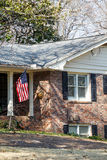 American Flag on Brick Home. An American flag on the porch of a small brick home Stock Images