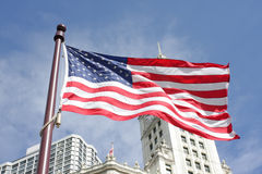 American Flag with buildings behind it Stock Photos