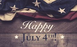 An American flag or bunting on a wooden background with July 4th greeting