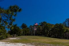 American Flag at Carolina Beach State Park Marina on the South end of Snows Cut in North Carolina. Dark blue sky and trees are the background of an American stock photos