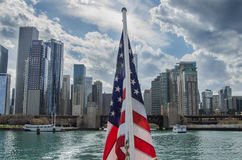 American Flag Centered on Chicago Skyline. The American flag from a tourist boat sits in the center of a view looking back at the Chicago urban skyline stock images