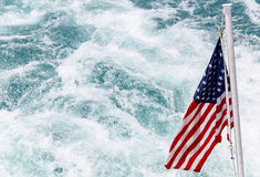 The American Flag. Chicago, USA - May 24, 2014: The American flag is waving over the wake of a ship Stock Image