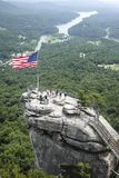 American Flag on Chimney Rock. Sightseers gather around an American Flag at the peak of Chimney Rock, North Carolina Stock Images