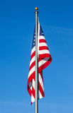 American flag on clear blue sky background. American flag with flag pole on clear blue sky background Royalty Free Stock Photography