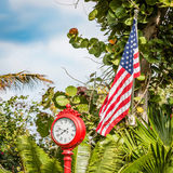 American flag with clock. On green palm background royalty free stock photo