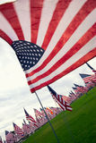 American Flag close up. An American flag waving in the wind curls around the camera, with hundreds of flags in the background Stock Photo
